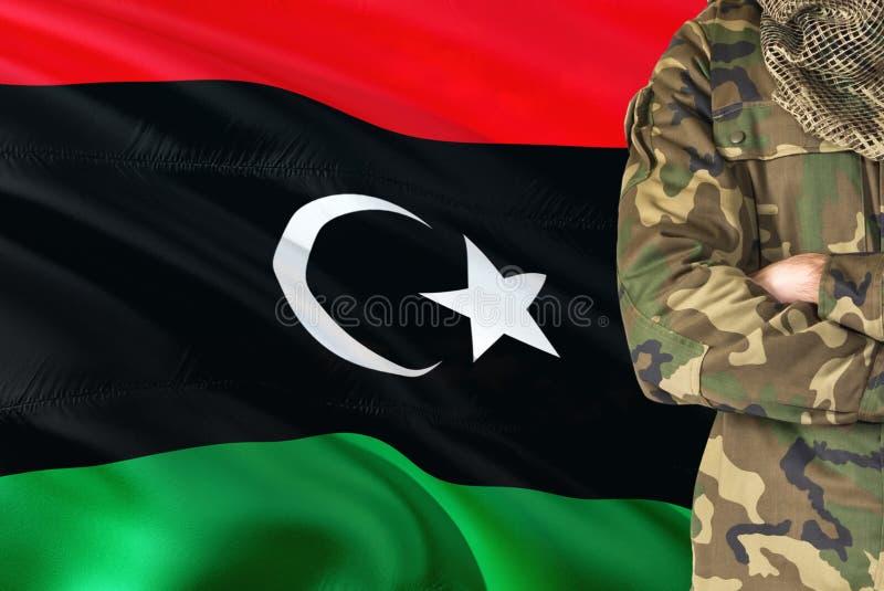 有全国挥动的旗子的横渡的胳膊利比亚士兵在背景-利比亚军事题材 免版税库存图片