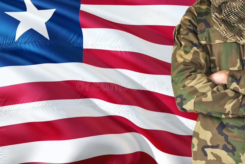 有全国挥动的旗子的横渡的胳膊利比里亚士兵在背景-利比里亚军事题材 图库摄影