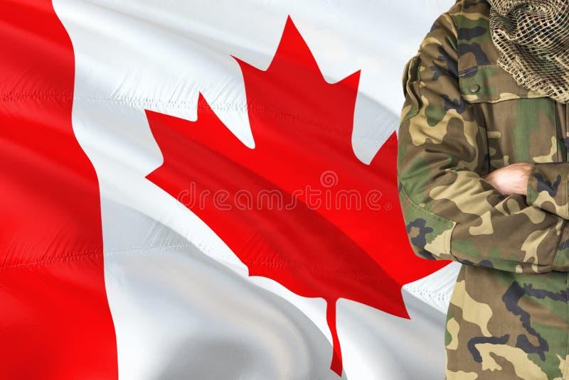 有全国挥动的旗子的横渡的胳膊加拿大士兵在背景-加拿大军事题材 免版税库存照片