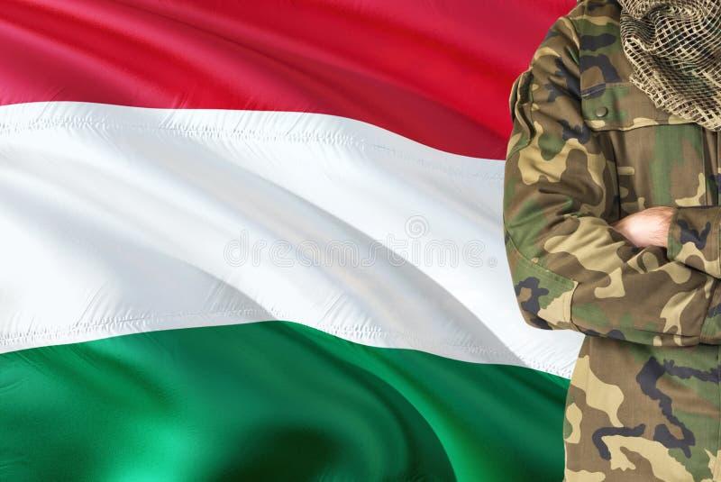 有全国挥动的旗子的横渡的胳膊匈牙利士兵在背景-匈牙利军事题材 库存照片