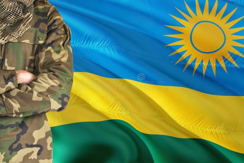 有全国挥动的旗子的横渡的胳膊卢旺达士兵在背景-卢旺达军事题材 库存图片