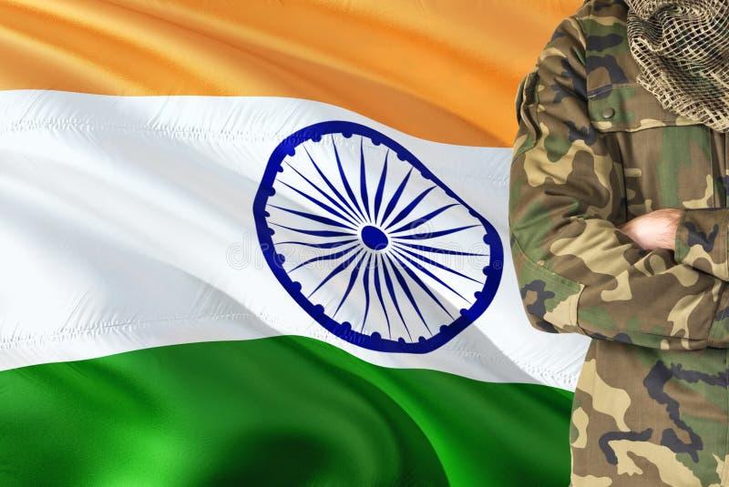 有全国挥动的旗子的横渡的胳膊印度士兵在背景-印度军事题材 库存图片