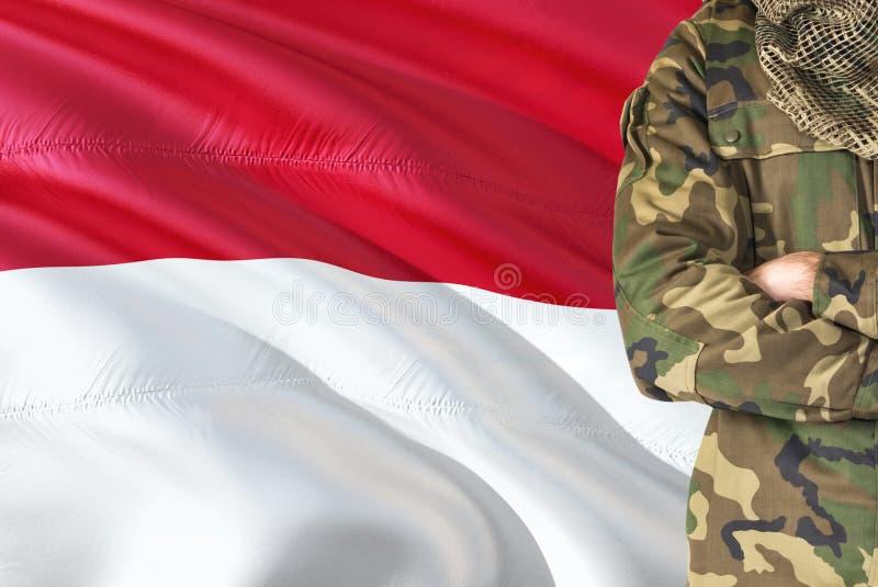 有全国挥动的旗子的横渡的胳膊印度尼西亚士兵在背景-印度尼西亚军事题材 免版税库存照片