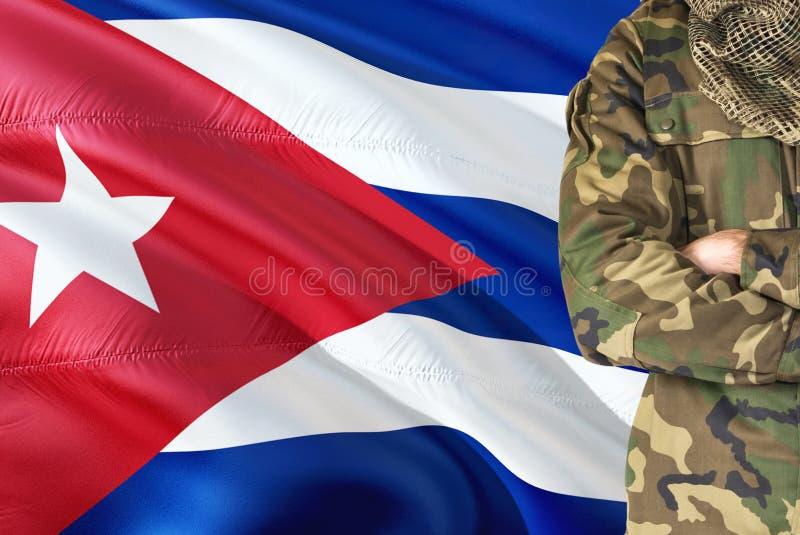 有全国挥动的旗子的横渡的胳膊古巴士兵在背景-古巴军事题材 图库摄影