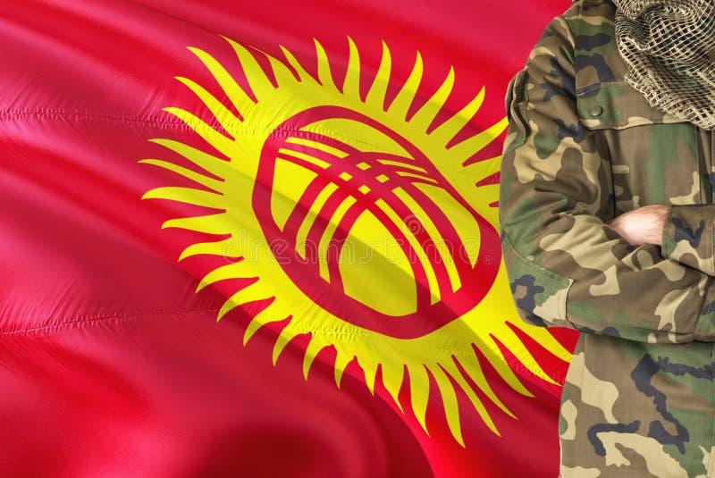 有全国挥动的旗子的横渡的胳膊吉尔吉斯士兵在背景-吉尔吉斯斯坦军事题材 免版税库存图片