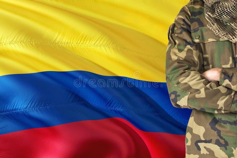 有全国挥动的旗子的横渡的胳膊哥伦比亚的战士在背景-哥伦比亚军事题材 库存图片