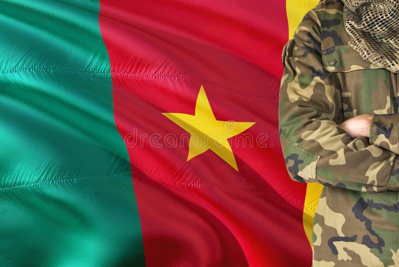 有全国挥动的旗子的横渡的胳膊喀麦隆战士在背景-喀麦隆军事题材 免版税图库摄影