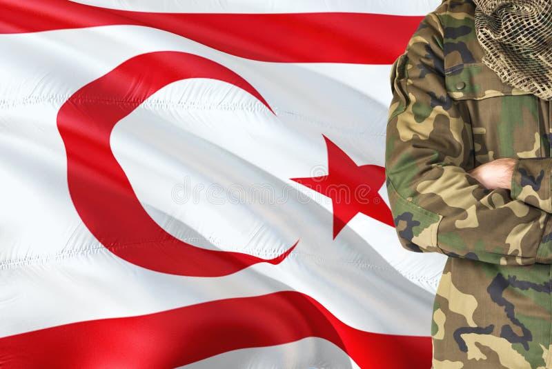 有全国挥动的旗子的横渡的胳膊土耳其士兵在背景-北赛普勒斯土耳其共和国军事题材 免版税库存照片