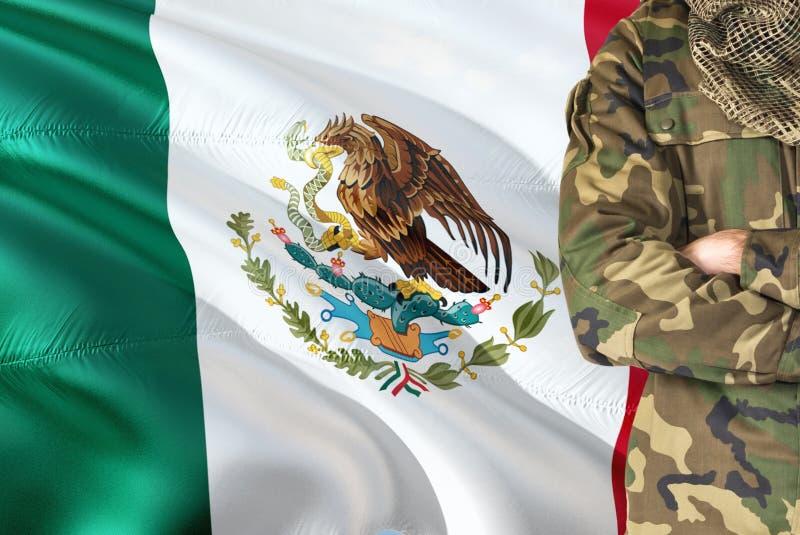 有全国挥动的旗子的横渡的胳膊墨西哥士兵在背景-墨西哥军事题材 免版税库存照片