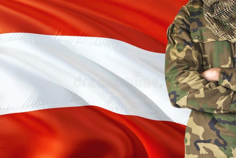 有全国挥动的旗子的横渡的胳膊奥地利士兵在背景-澳大利亚军事题材 库存照片