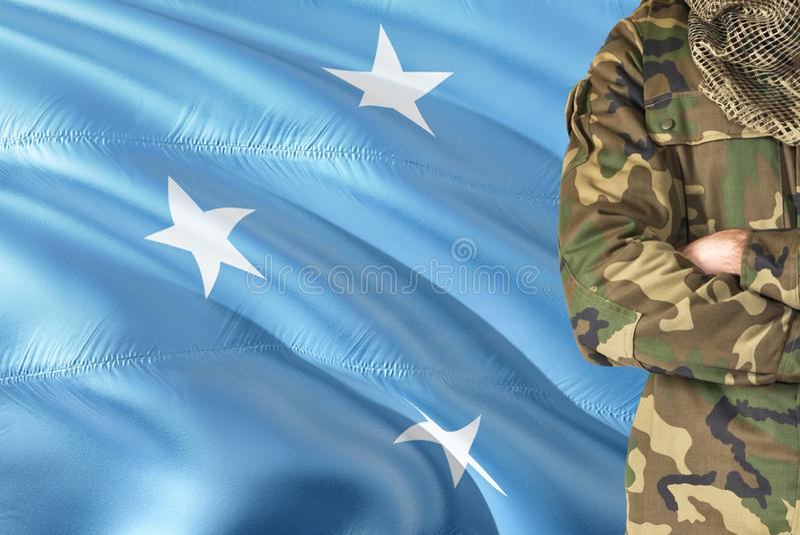 有全国挥动的旗子的横渡的胳膊密克罗尼西亚战士在背景-密克罗尼西亚军事题材 库存照片