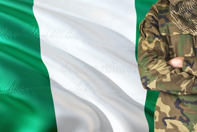 有全国挥动的旗子的横渡的胳膊尼日利亚士兵在背景-尼日利亚军事题材 图库摄影