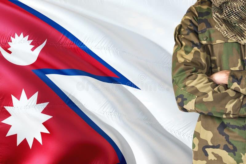 有全国挥动的旗子的横渡的胳膊尼泊尔士兵在背景-尼泊尔军事题材 库存图片