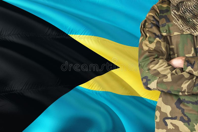 有全国挥动的旗子的横渡的胳膊巴哈马群岛的战士在背景-巴哈马军事题材 免版税库存照片