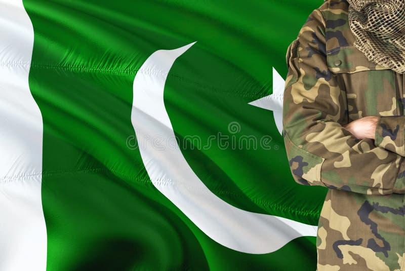 有全国挥动的旗子的横渡的胳膊巴基斯坦士兵在背景-巴基斯坦军事题材 库存照片