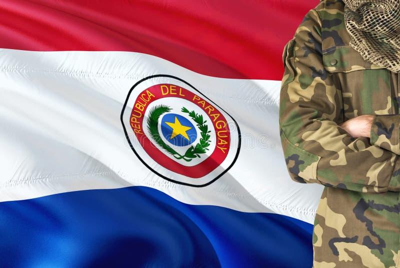 有全国挥动的旗子的横渡的胳膊巴拉圭战士在背景-巴拉圭军事题材 免版税库存照片