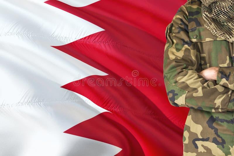 有全国挥动的旗子的横渡的胳膊巴林士兵在背景-巴林军事题材 免版税库存图片
