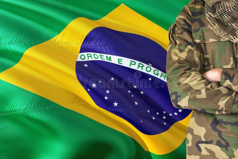 有全国挥动的旗子的横渡的胳膊巴西士兵在背景-巴西军事题材 库存图片