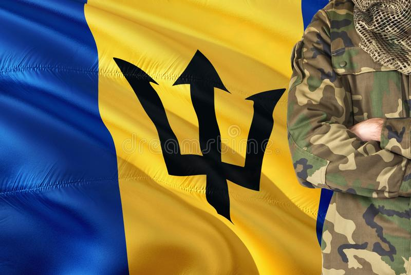 有全国挥动的旗子的横渡的胳膊巴贝多战士在背景-巴巴多斯军事题材 免版税库存照片