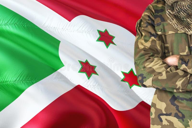 有全国挥动的旗子的横渡的胳膊布隆迪战士在背景-布隆迪军事题材 免版税库存照片