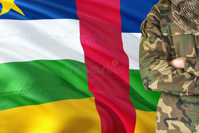 有全国挥动的旗子的横渡的胳膊战士在背景-中非共和国军事题材 免版税库存照片