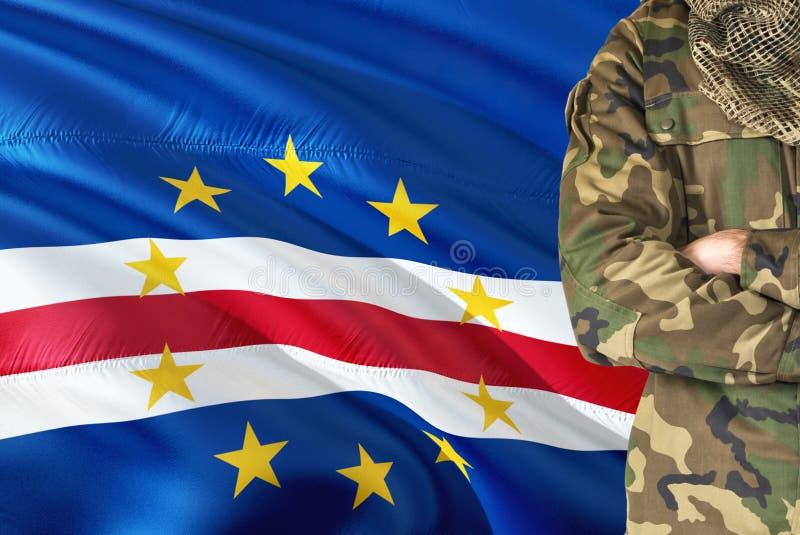 有全国挥动的旗子的横渡的胳膊战士在背景-佛得角军事题材 免版税库存照片