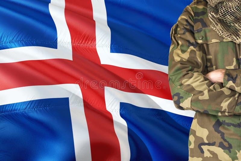 有全国挥动的旗子的横渡的胳膊战士在背景-冰岛军事题材 图库摄影