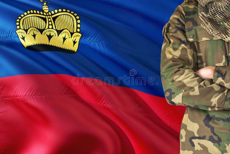 有全国挥动的旗子的横渡的胳膊战士在背景-列支敦士登军事题材 库存图片
