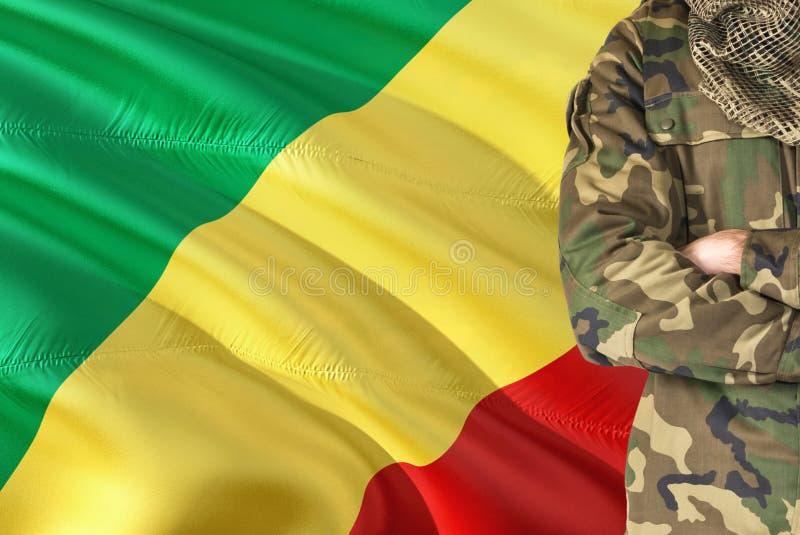 有全国挥动的旗子的横渡的胳膊战士在背景-刚果共和国军事题材 免版税库存照片