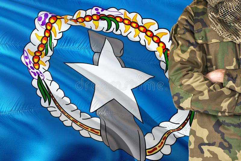 有全国挥动的旗子的横渡的胳膊战士在背景-北马里亚纳群岛军事题材 免版税库存照片