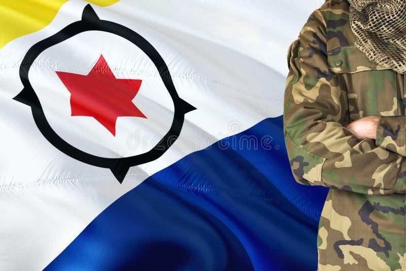 有全国挥动的旗子的横渡的胳膊战士在背景-博内尔岛军事题材 库存照片