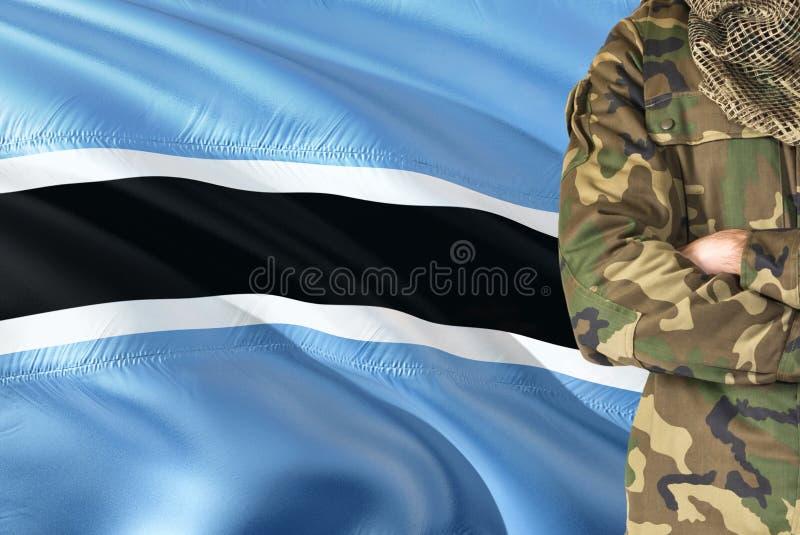 有全国挥动的旗子的横渡的胳膊战士在背景-博茨瓦纳军事题材 库存图片