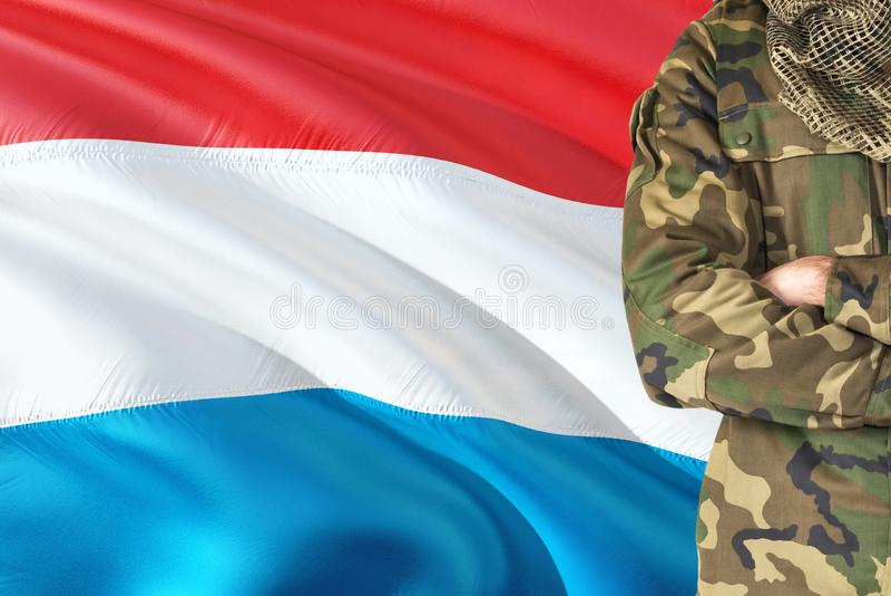 有全国挥动的旗子的横渡的胳膊战士在背景-卢森堡军事题材 图库摄影