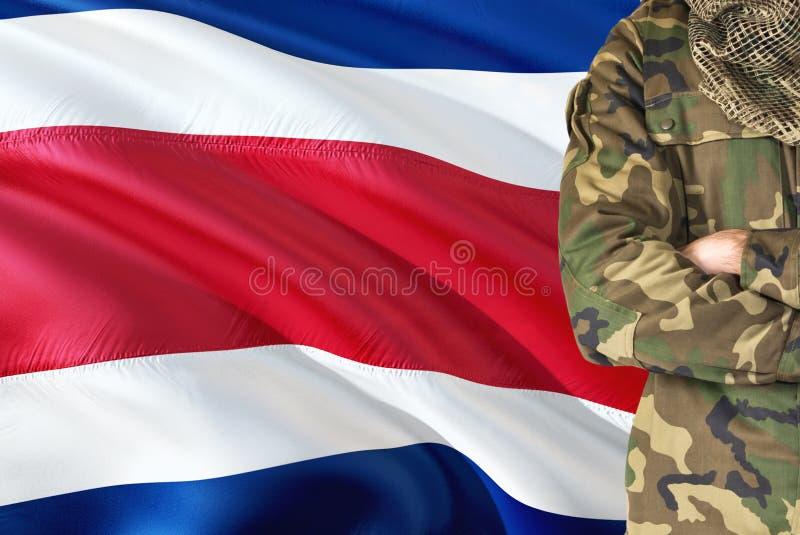 有全国挥动的旗子的横渡的胳膊战士在背景-哥斯达黎加军事题材 免版税库存照片