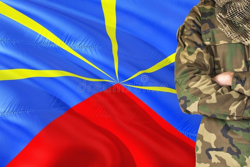 有全国挥动的旗子的横渡的胳膊战士在背景-团聚军事题材 免版税库存照片