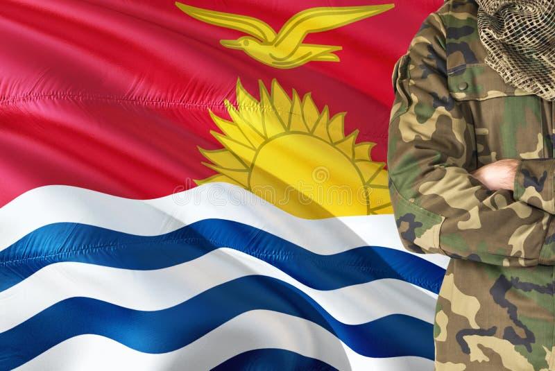有全国挥动的旗子的横渡的胳膊战士在背景-基里巴斯军事题材 免版税库存照片