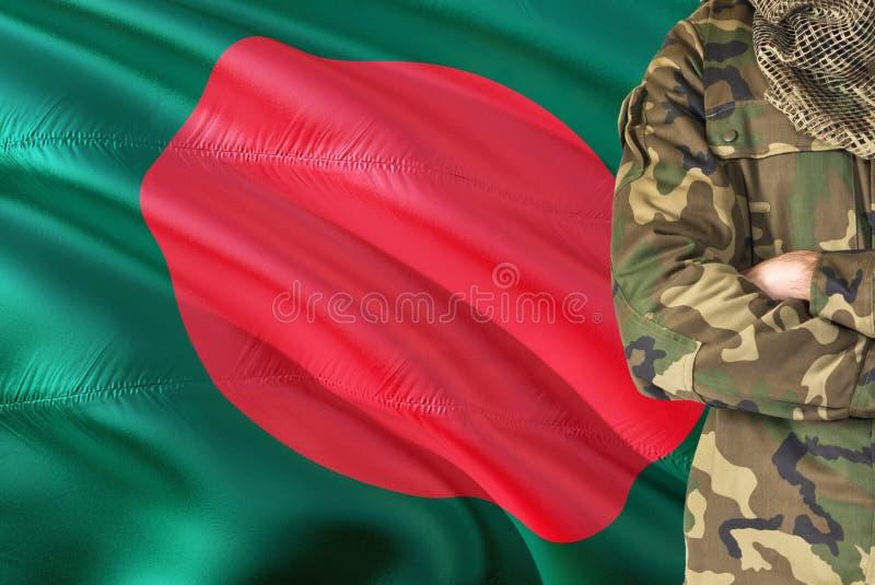 有全国挥动的旗子的横渡的胳膊战士在背景-孟加拉国军事题材 免版税库存照片