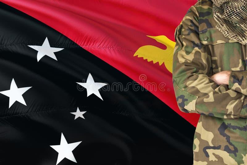 有全国挥动的旗子的横渡的胳膊战士在背景-巴布亚新几内亚军事题材 免版税库存照片