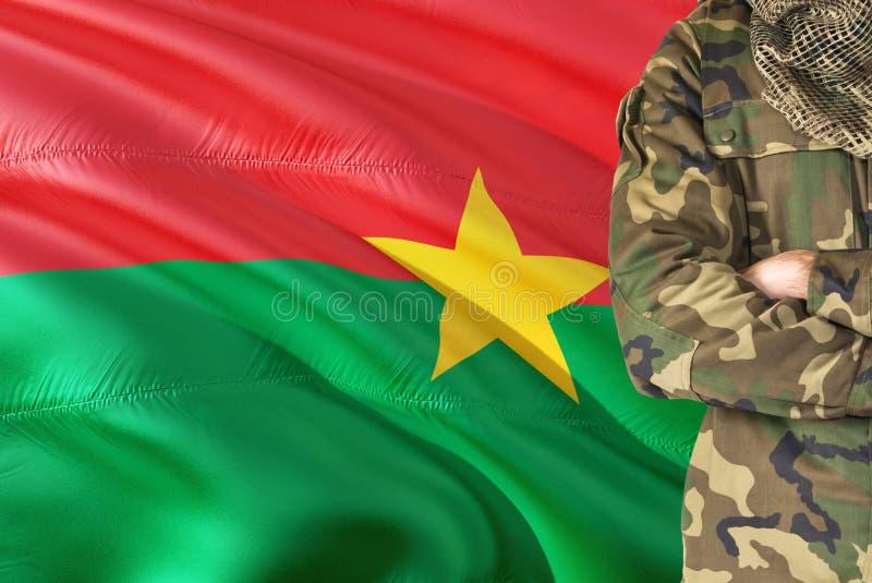 有全国挥动的旗子的横渡的胳膊战士在背景-布基纳法索军事题材 免版税图库摄影