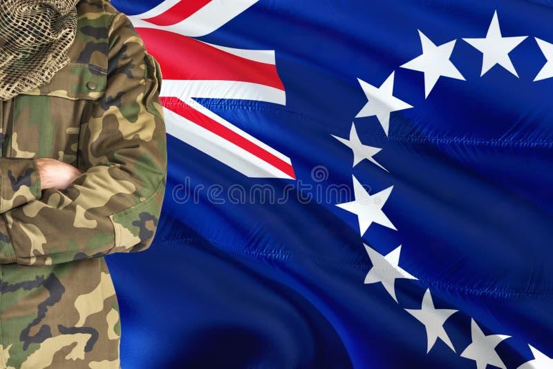 有全国挥动的旗子的横渡的胳膊战士在背景-库克群岛军事题材 免版税图库摄影
