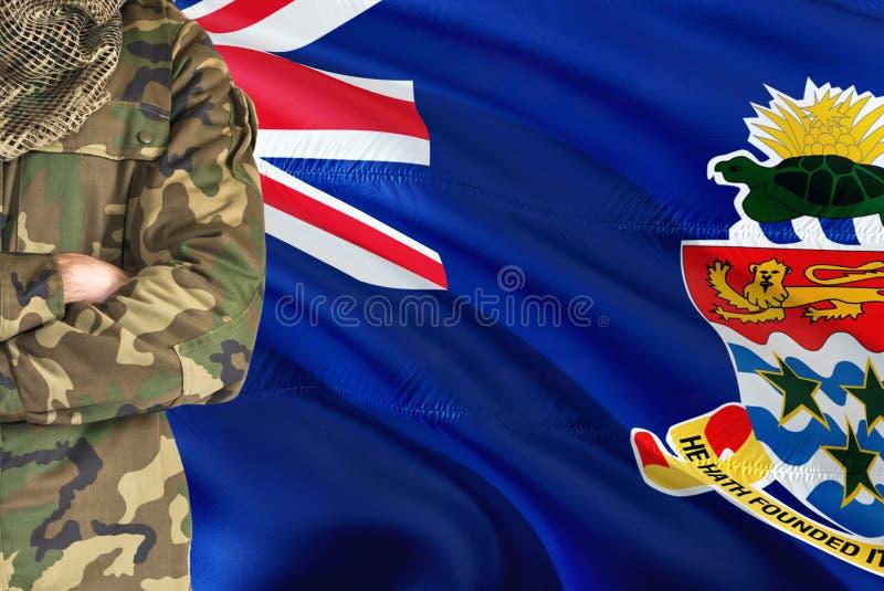 有全国挥动的旗子的横渡的胳膊战士在背景-开曼群岛军事题材 库存图片