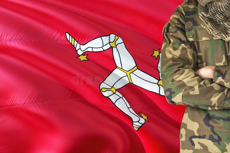 有全国挥动的旗子的横渡的胳膊战士在背景-曼岛军事题材 免版税库存图片