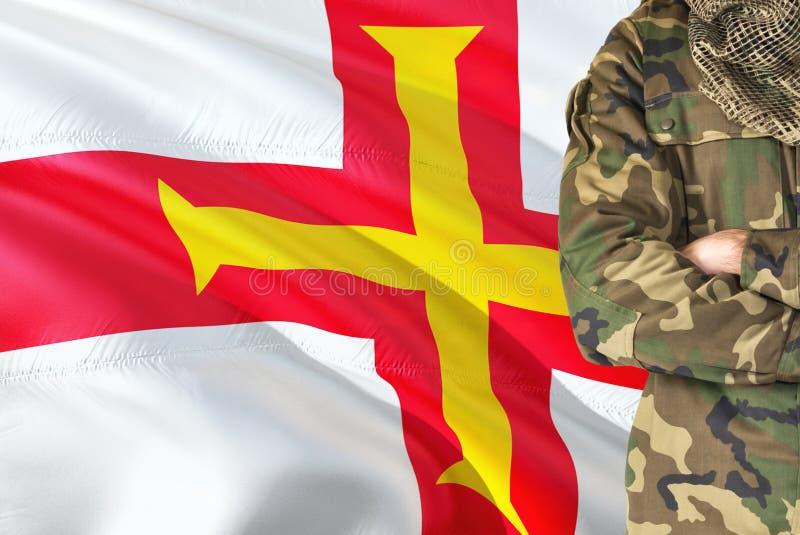 有全国挥动的旗子的横渡的胳膊战士在背景-根西岛军事题材 免版税库存照片
