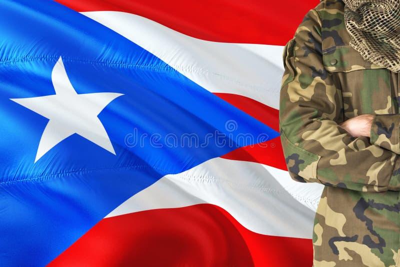 有全国挥动的旗子的横渡的胳膊战士在背景-波多黎各军事题材 图库摄影