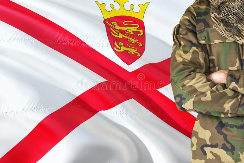 有全国挥动的旗子的横渡的胳膊战士在背景-泽西军事题材 库存图片