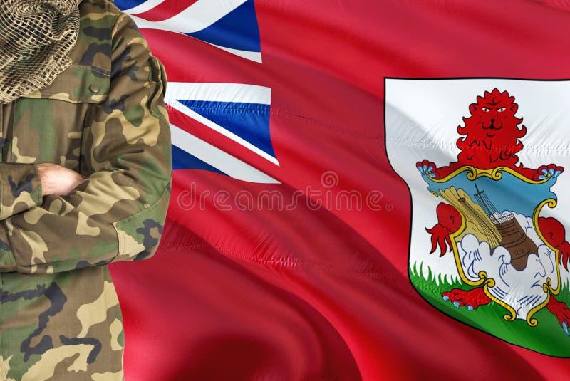 有全国挥动的旗子的横渡的胳膊战士在背景-百慕大军事题材 库存图片