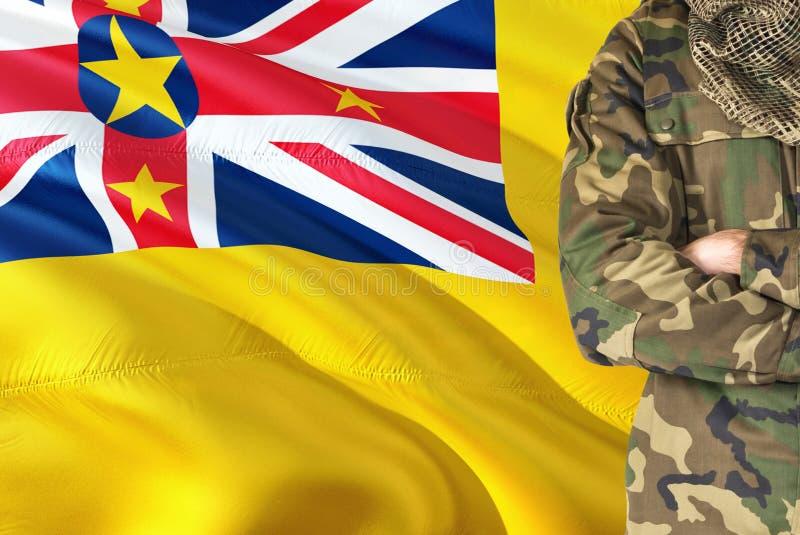 有全国挥动的旗子的横渡的胳膊战士在背景-纽埃军事题材 图库摄影