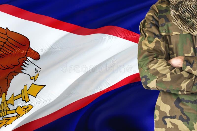 有全国挥动的旗子的横渡的胳膊战士在背景-美属萨摩亚军事题材 免版税库存照片