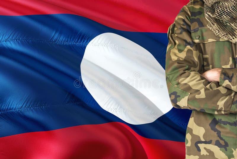 有全国挥动的旗子的横渡的胳膊战士在背景-老挝军事题材 免版税库存图片