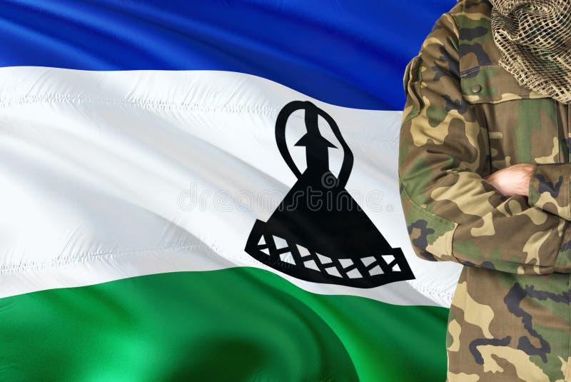 有全国挥动的旗子的横渡的胳膊战士在背景-莱索托军事题材 图库摄影